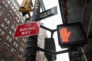 Signs on street corner that say Wrong Way, One Way and a red hand stop light.