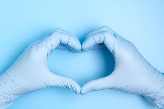 blue hand gloves making heart shape on blue background for care, love or support medical team