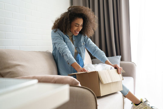 Excited african young woman shopper opening parcel box at home. Happy satisfied ethnic girl customer receiving online shop purchase by postal shipping, unpacking delivery receiving gift sit on sofa.