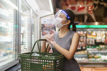 Woman wearing gloves, face shield and mask. Panic shopping during the corona virus pandemic.