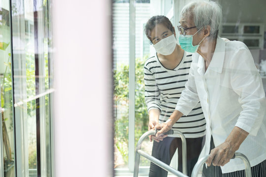 Asian daughter take care of senior mother,elderly woman is looking outside through window feeling bored,depressed,stressed,life depression of old people,stay home during Covid-19,Coronavirus pandemic