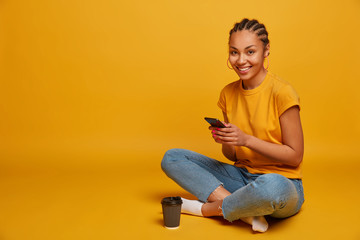 Photo of relaxed dark skinned girl happy to receive message from lover, holds mobile phone, watches funny cute video, sits in lotus pose, drinks takeaway coffee, isolated on yellow background