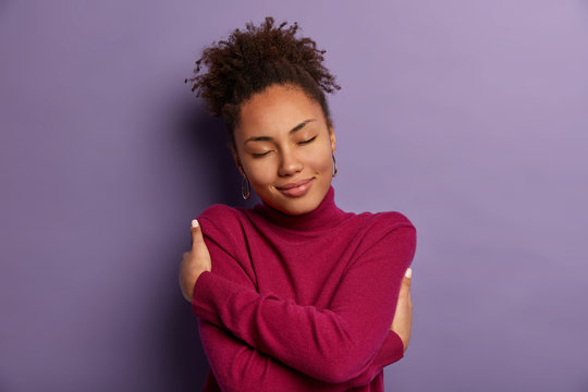 I love myself. Tender romantic woman embraces own body, hugs herself, closes eyes from pleasure, wears soft turtleneck just for cold weather, feels comfort, stands indoor against purple wall