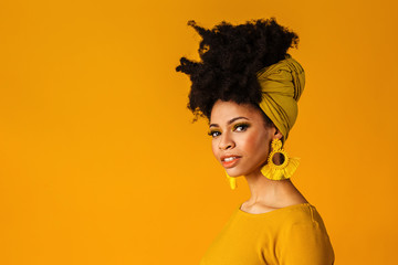 Portrait of a serious young woman with big yellow tassel beaded earrings and afro hair wrapped with...