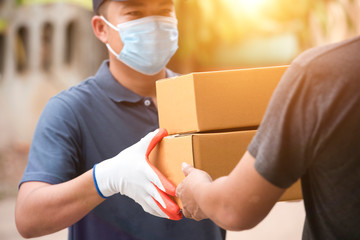 People wearing gray T-shirts are delivering parcels to satisfied customers. Friendly workers, high quality delivery service in Asia
