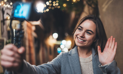 Fotomurales - Female tourist blogger shooting video for vlog social media with digital camera showing hi. Smiling woman vlogger taking photo selfie on background light night city illuminations