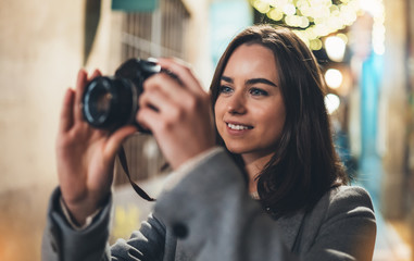 Fotomurales - Photographer girl with retro camera take photo on background bokeh light in night city, Blogger photo hobby. Outdoor portrait of young smile woman hold in hands video technology.