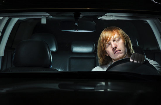 Young man dozing off while driving at night