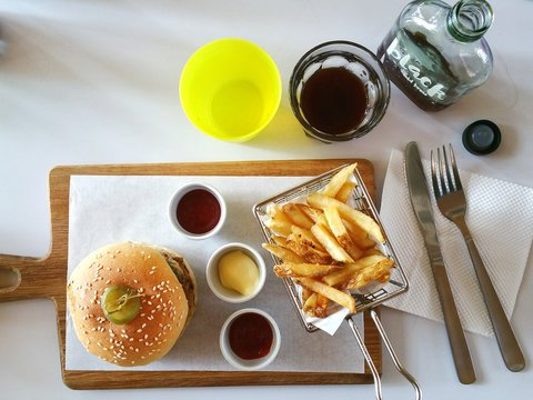 High Angle View Of Burger On Cutting Board Over Table