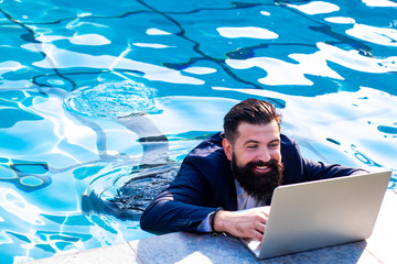 Business man in suit with laptop on swimming pool. Funny businessman relaxing with laptop.