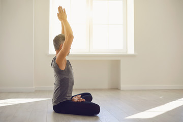 Yoga man. Bearded guy is practicing yoga in a lotus position sitting in a studio