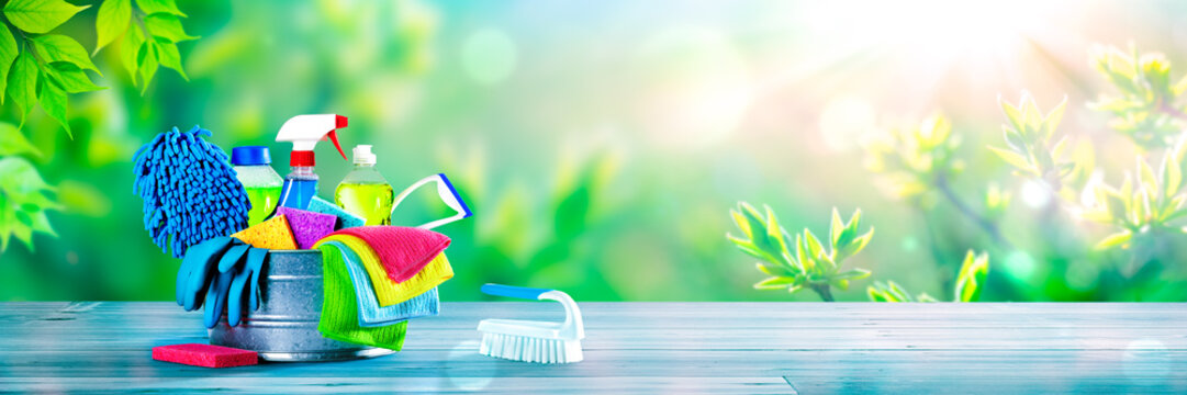 Bucket Of Cleaning Supplies On Wooden Table With Fresh Spring Background - Cleaning Services Concept