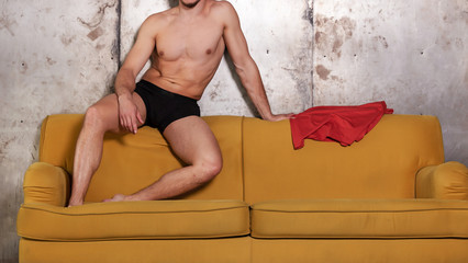 Good looking naked man sitting on the couch revealing sixpack abs and wearing briefs. Black underwear for men.