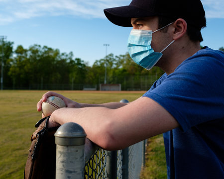 Images of young man wearing a COVID-19 mask at a closed baseball field.