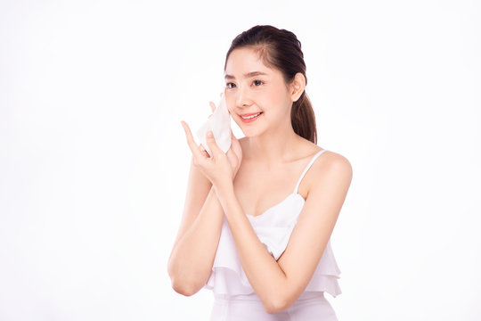 Beautiful young Asian woman with fresh face holding cleansing facial sheet wipe with smile. The girl portrait, isolated on white background. Facial cosmetic make up cleaning product advertisement.