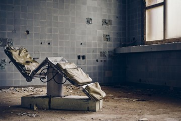 Abandoned dental room with an old chair and ruined walls under the lights