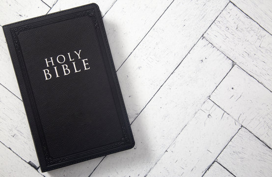 A Black Holy BIble on a White Wooden Table