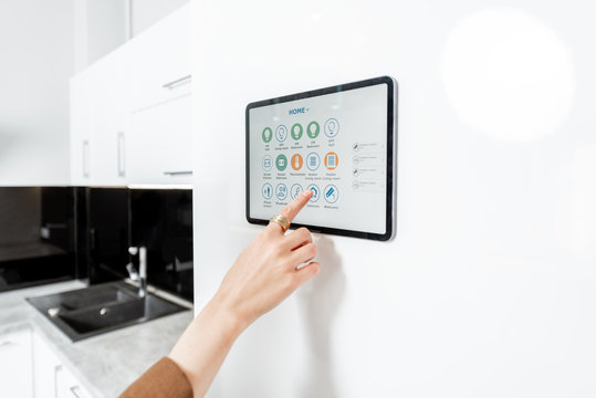 Controlling kitchen appliances with a digital tablet on the wall with launched smart home application, close-up. Smart home concept