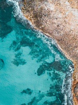 Amazing eagle-eye vertical shot of a sea colliding the shore