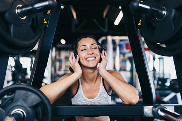Young attractive woman after successful workout in modern fitness gym dancing, smiling and singing....