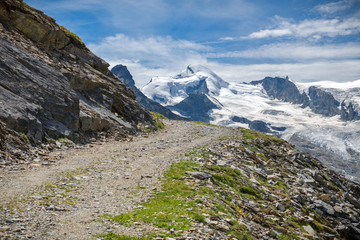 Wall Mural - Walking trail with beautiful views on Fee Glacier located above Saas-Fee village in Switzerland