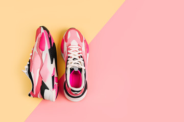 Bright female sneakers on pink background. Fashion blog or magazine concept. Women's shoes, trendy sneakers, fashion, style, lifestyle. Flat lay top view copy space minimal background..