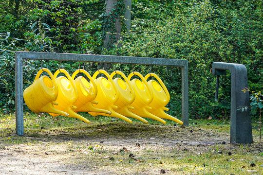 Reihe gelber Giesskannen