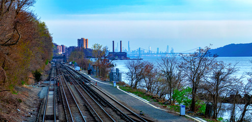 Waterfront view in Hastings-On-Hudson, NY, with train tracks and the Hudson River and New York City in the background