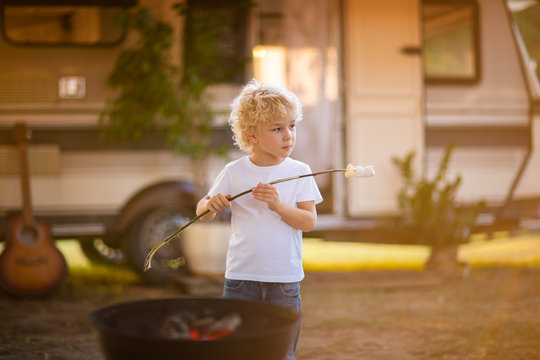 Cute curly boy having a picnic at camping near the trailer