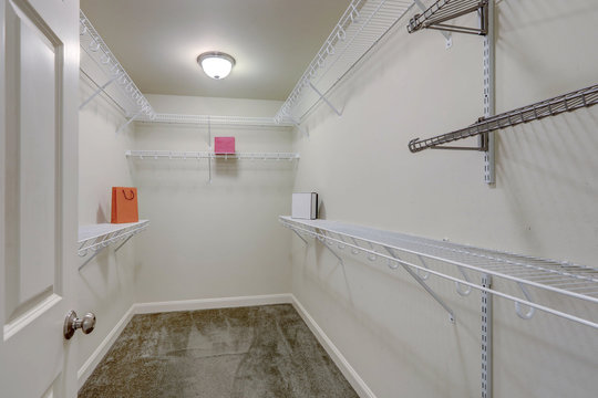 Large empty master bedroom closet with simple metal adjustable shelves.