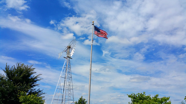 Low Angle View Of American Flag By Traditional Windmill Against Sky