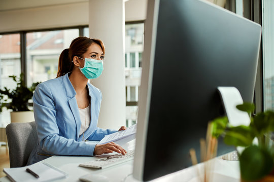 Businesswoman with face mask using computer while working on reports in the office.