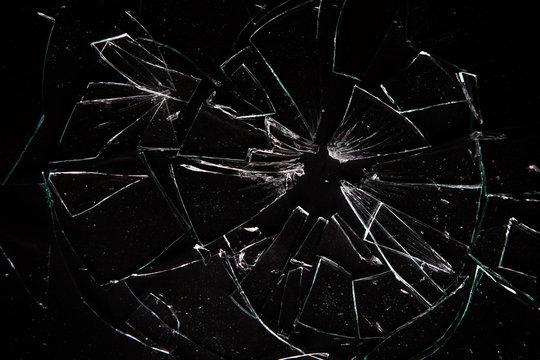 Broken glass on black background with lots of glass splinters