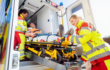 Paramedics putting injured man on stretcher in ambulance car Fototapete