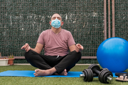 Mature man doing yoga and pilates at home. Healthy lifestyle concept, wellbeing, safety while the coronavirus pandemic.