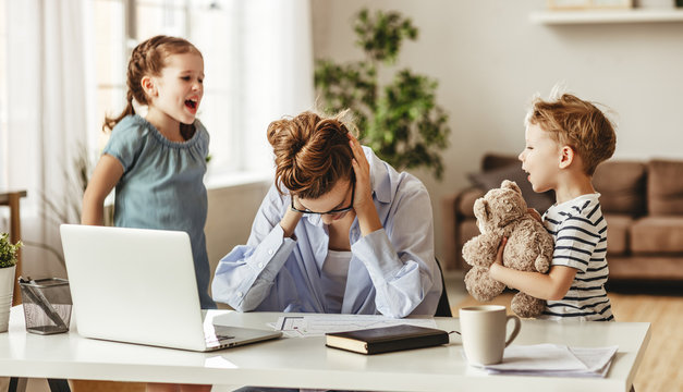 Little naughty children distracting busy young woman from work on laptop at home