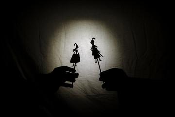 teatro de sombras chinas para niños proyectadas en una sabana de cama, temática de San Jorge, 23 de abril. marionetas, se ve la mano que los manipula. Dragón, hada, princesa, castillo. Cuenta cuentos