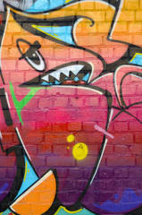 Abstract colorful fragment of graffiti paintings on old brick wall. Street-art composition with...