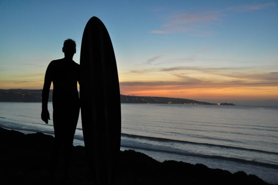 Silhouette Man With Surfboard Standing At Beach Against Sky During Sunset