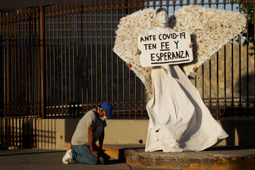 """A man prays next to a religious activist from the evangelical church """"Psalm 100"""", dressed as an angel outside a hospital caring for patients with the coronavirus disease (COVID-19), in Ciudad Juarez"""