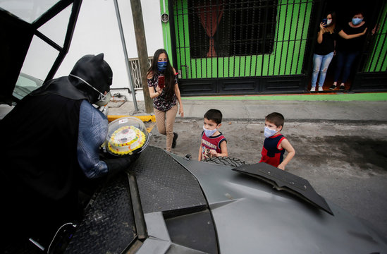 Mexican lawyer Candelario Maldonado, dressed as Batman, gives a birthday cake to children wearing face masks in front of their home, during the global outbreak of the coronavirus disease COVID-19, in Monterrey