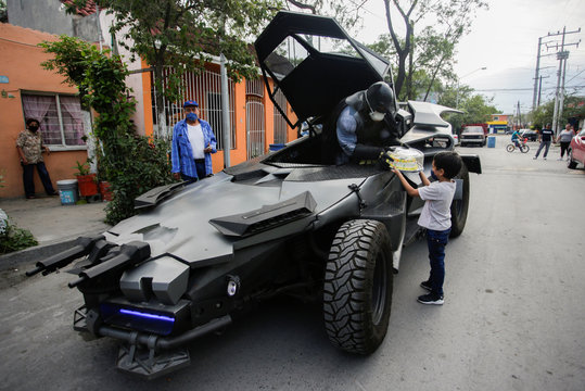 Mexican lawyer Candelario Maldonado, dressed up as the fictional character Batman, gives a birthday cake to a child wearing face mask in front of his home, during the global outbreak of the coronavirus disease (COVID-19), in Monterrey