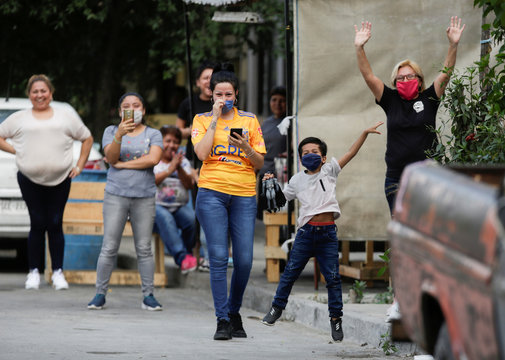 People react as Mexican lawyer Candelario Maldonado, dressed up as the fictional character Batman, arrives to give a birthday cake to a child at their home during the global outbreak of the coronavirus disease (COVID-19) in Monterrey
