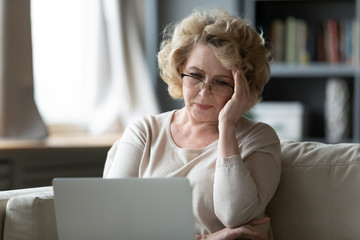Old woman sit on couch using laptop looks at screen feels stressed not understand need assistance with new app, wrong password, exhausted, older generation and difficulties with modern tech concept