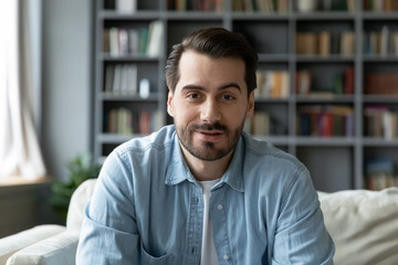 Fototapeta Head shot millennial guy sit on sofa in living room makes video call looks at camera, conversation by distant videocall, distance hiring job interview process, tutor and trainee study on-line concept