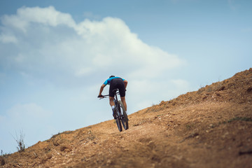Mountain biker cycling, training and going up a steep climb.