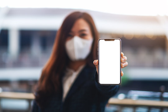 Mockup image of a woman wearing protective face mask, showing mobile phone with blank white screen while standing in front of red and white warning tape area for the spread of Covid-19 concept
