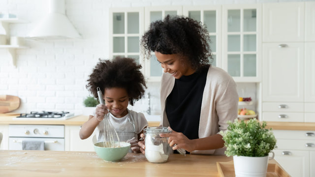 Loving young African American mother teach small biracial daughter bake in kitchen, happy caring ethnic mom and little girl child preparing pancakes or biscuits, make breakfast at home together