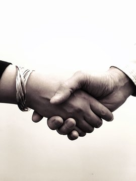 Cropped Image Of Man And Woman Shaking Hands Against White Background