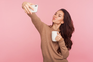 Portrait of stunning happy young woman holding cup of coffee and kissing air, looking seductively while taking selfie on smartphone, having online conversation with lover. studio shot, pink background